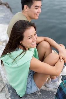 Homem sorridente e mulher ao ar livre à beira do lago