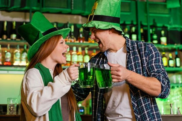Homem sorridente e mulher comemorando st. dia de patrick com bebidas