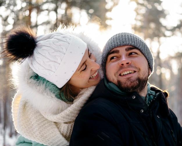 Homem sorridente e mulher juntos ao ar livre no inverno