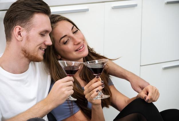 Homem sorridente e mulher sentada no chão da cozinha e segurando copos de coquetéis. casal romântico passar um tempo juntos, se divertir e beber em casa.