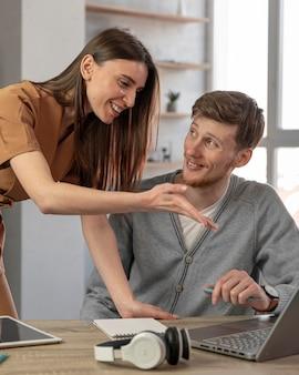 Homem sorridente e mulher trabalhando com laptop e fones de ouvido