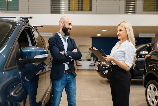 Homem sorridente e vendedora na concessionária. cliente e vendedor em showroom de veículos, homem comprando transporte, concessionária de automóveis