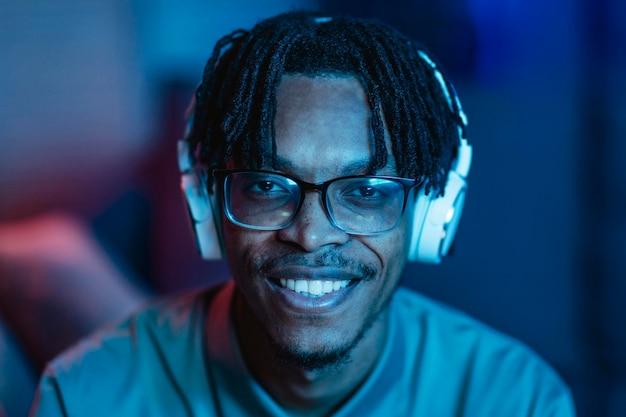 Homem sorridente em casa usando fones de ouvido