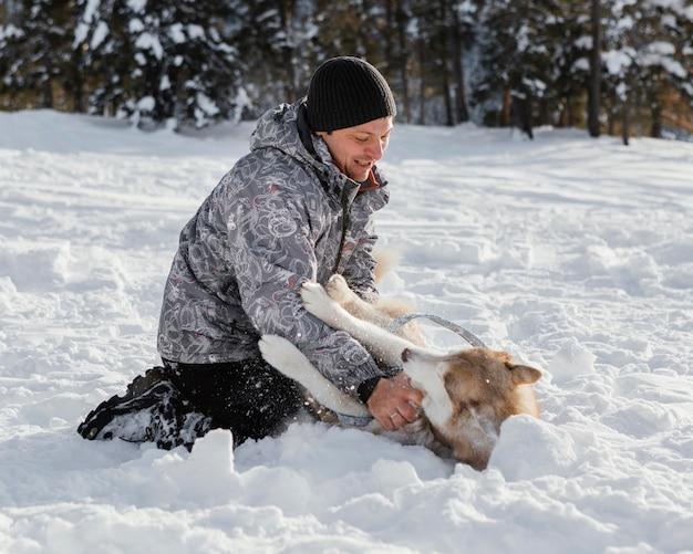 Homem sorridente em cena completa brincando com um cachorro