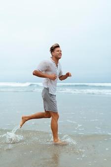 Homem sorridente em cena completa correndo na praia