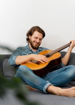 Homem sorridente em cena completa tocando violão