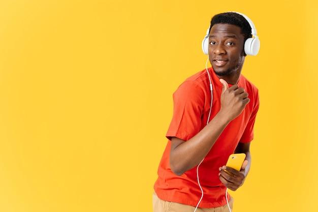 Homem sorridente em fones de ouvido com um telefone nas mãos em um fundo amarelo