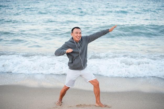 Homem sorridente em foto completa à beira-mar