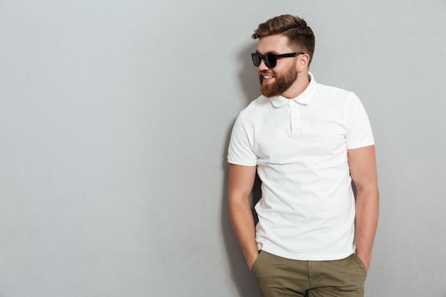 Homem sorridente em óculos de sol posando