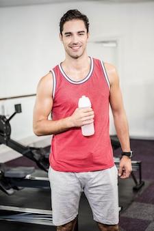 Homem sorridente em pé e segurando a garrafa de água no ginásio