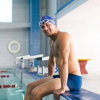 Homem sorridente em pé na beira da piscina