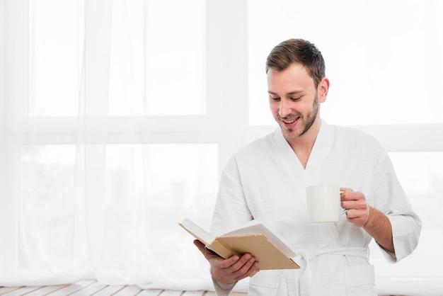 Homem sorridente em roupão segurando livro e xícara