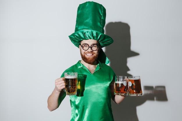 Homem sorridente em traje de st. patriks segurando copos