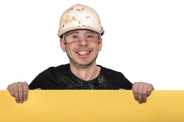 Homem sorridente em um capacete de construção e óculos de proteção. sujo depois do trabalho. possui uma placa amarela para texto publicitário. fundo branco isolado. conceito de publicidade de serviços de construção.