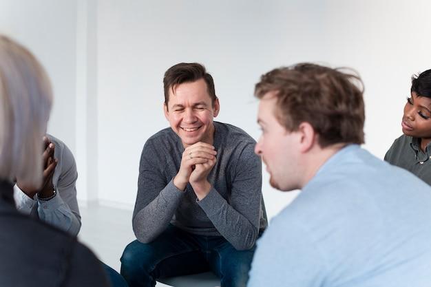Homem sorridente em um grupo de pacientes