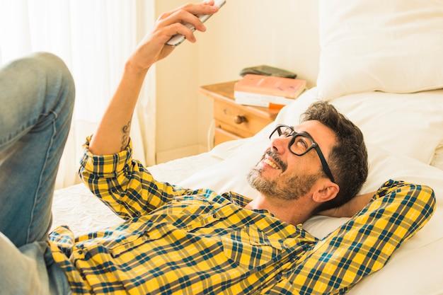 Homem sorridente, encontrar-se cama, olhar, telefone móvel
