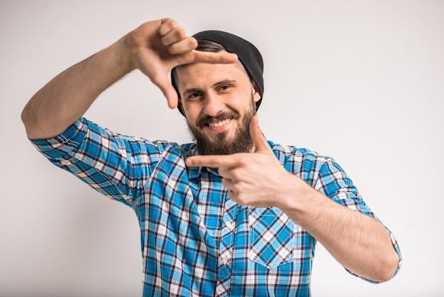 Homem sorridente, enquadrando a foto com os dedos