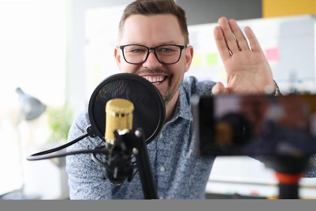 Homem sorridente ergueu a mão em sinal de gratidão e escreveu um vídeo para um blog líder de programas online