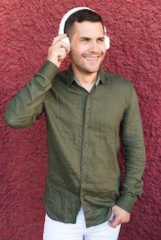 Homem sorridente, escutar, música, em, headphone, ficar, perto, vermelho, áspero, parede