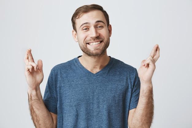 Homem sorridente esperançoso fazendo desejo, cruzar os dedos boa sorte