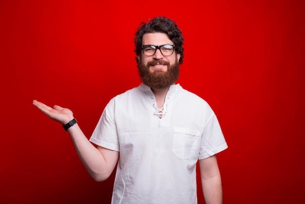 Homem sorridente está apresentando algo com a mão no vermelho.