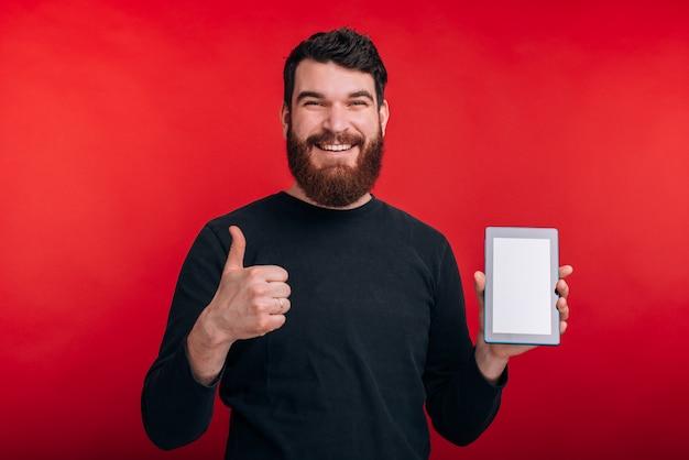 Homem sorridente está mostrando o polegar para cima e a tela em branco de um tablet na parede vermelha