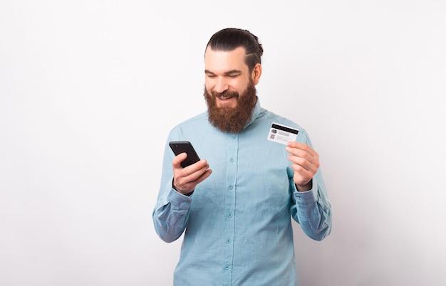 Homem sorridente está usando a internet ou o banco móvel em seu telefone enquanto segura o cartão.