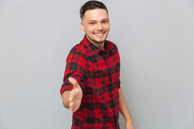 Homem sorridente estende a mão para um aperto de mão