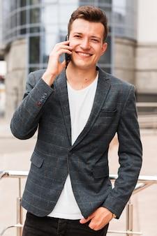 Homem sorridente falando ao telefone a caminho do trabalho
