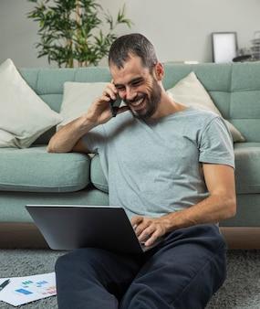 Homem sorridente falando ao telefone em casa enquanto trabalha no laptop