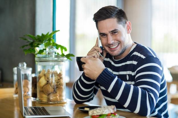 Homem sorridente, falando no celular enquanto tomando café no café