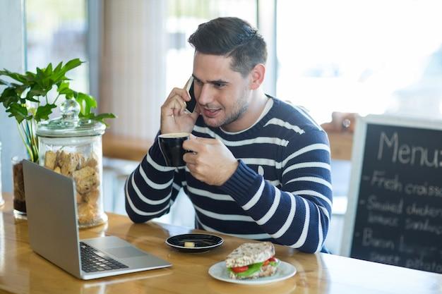 Homem sorridente, falando no celular enquanto tomando café
