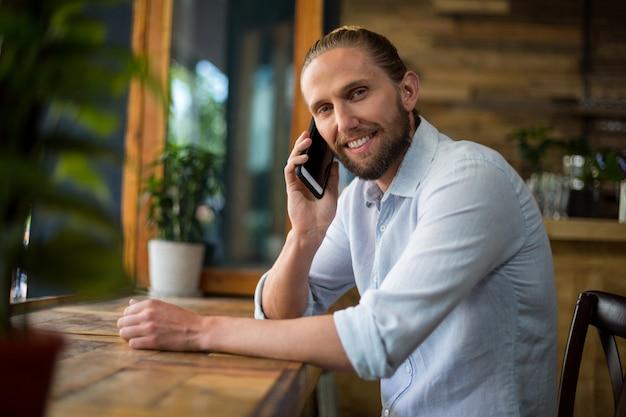 Homem sorridente, falando no celular no café