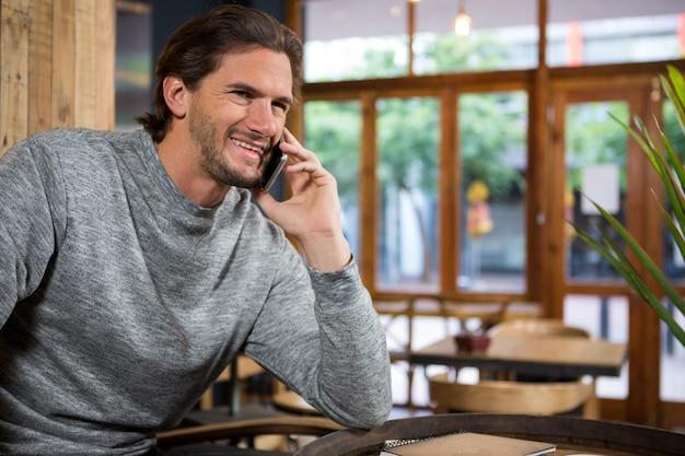 Homem sorridente falando no smartphone em uma cafeteria
