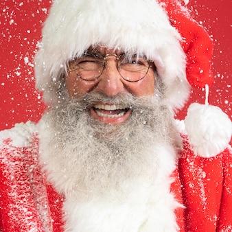 Homem sorridente fantasiado de papai noel com neve