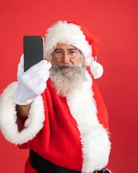 Homem sorridente fantasiado de papai noel com smartphone