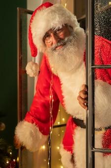 Homem sorridente fantasiado de papai noel entrando em casa pela janela