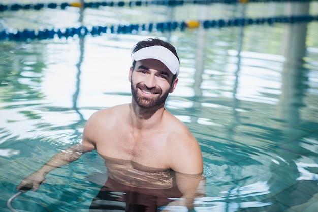 Homem sorridente fazendo bicicleta subaquática na piscina