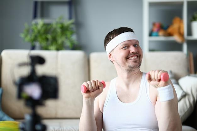 Homem sorridente fazendo exercício para as mãos com halteres