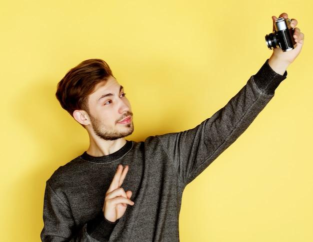 Homem sorridente fazendo selfie foto parede amarela