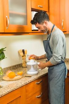 Homem sorridente fazendo suco de laranja usando um espremedor de mão na cozinha