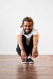 Homem sorridente fazendo um agachamento