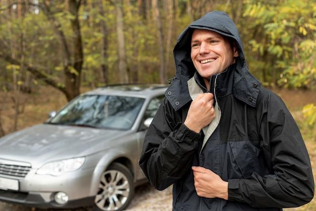 Homem sorridente, fechando sua jaqueta de inverno