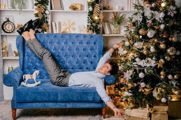 Homem sorridente feliz em roupas elegantes, deitado no sofá azul com árvore de cristmas no fundo. macho positivo que relaxa no sofá no estúdio com decorações do ano novo