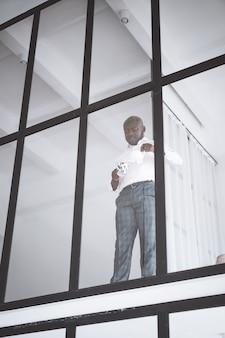 Homem sorridente feliz empresário de sucesso americano africano se derrama bebida no copo, ele está feliz a ...