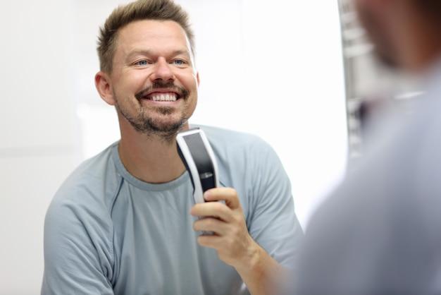 Homem sorridente fica na frente de um espelho e tem uma lâmina de barbear nas mãos.