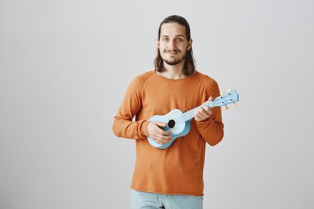 Homem sorridente fofo tocando ukulele
