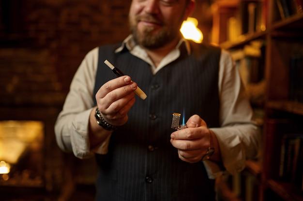 Homem sorridente fuma cigarro com porta-voz, estante e rico interior de escritório em segundo plano. cultura de fumar tabaco, sabor específico