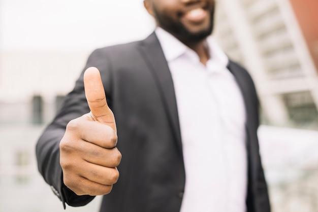 Homem sorridente gesticulando polegar para cima