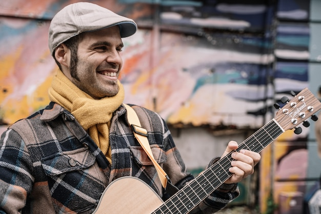 Homem sorridente guitarrista tocando na rua
